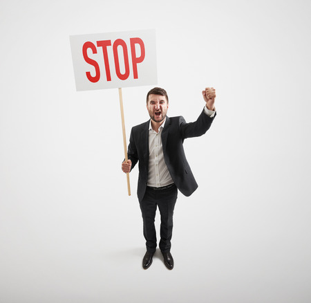 remonstrance: view from above of screaming businessman holding placard with stop sign over light grey background