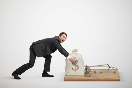 avidity: amazed man in formal wear reaching his hands to take bag with money in big mousetrap over light grey background