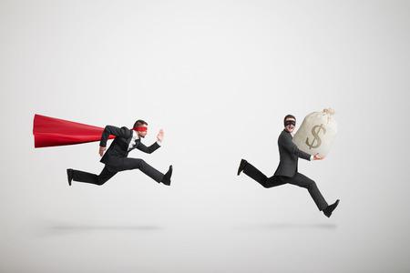 ladron: ladrón robó la bolsa con el dinero y huir de superman sobre fondo gris claro Foto de archivo