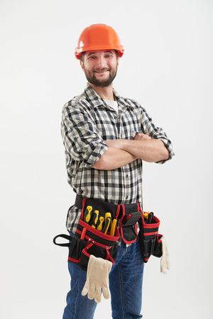 obrero: Obrero sonriente confidente con herramientas en el casco anaranjado que se coloca sobre la luz
