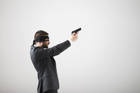 sighting: Sideview of man in formal wear with gun looking up and sighting over light grey  Stock Photo