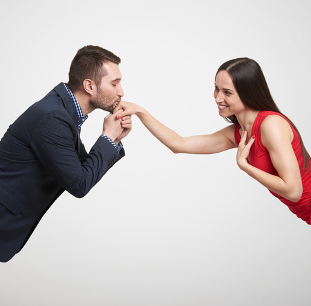 man in formal wear kissing hand of beautiful smiley woman in red dress over light grey background Stock Photo