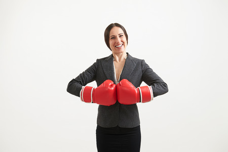 intimidate: Cheerful businesswoman in red boxing gloves looking at camera over light  Stock Photo