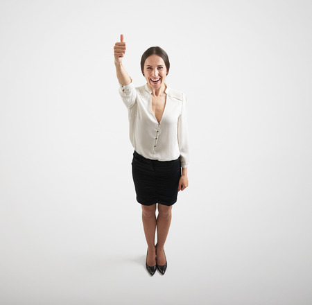 view from above of smiley woman in formal wear with thumbs up over light grey background