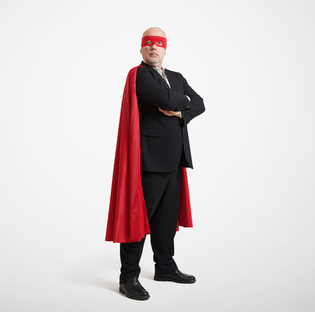 super hero: confident senior businessman wearing like super hero in red mask and cloak over light grey background