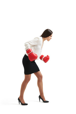 intimidate: serious businesswoman in formal wear and red gloves standing in boxing pose and looking down over light background