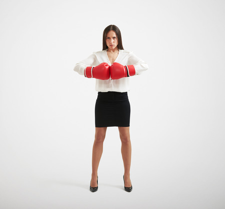 intimidate: full length portrait of confident businesswoman with red gloves looking at camera over light background Stock Photo