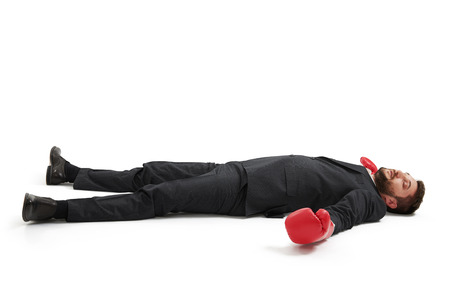 defeated businessman in formal wear and red boxing gloves lying on the floor over light grey background