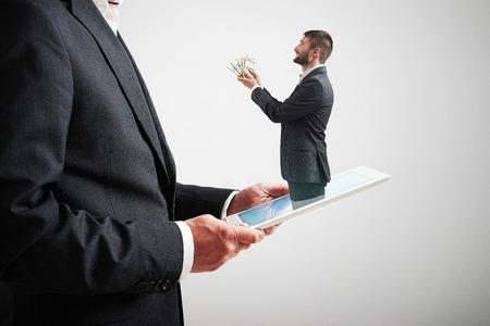 smiley man stapte uit de tablet pc en het aanbieden van geld aan de grote man in formele slijtage over lichtgrijze achtergrond Stockfoto