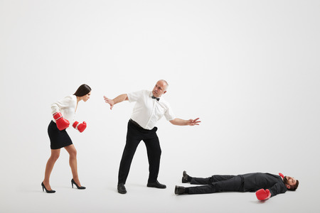 referee holding angry businesswoman in boxer gloves and counting down to knocked out businessman over light grey background Фото со стока