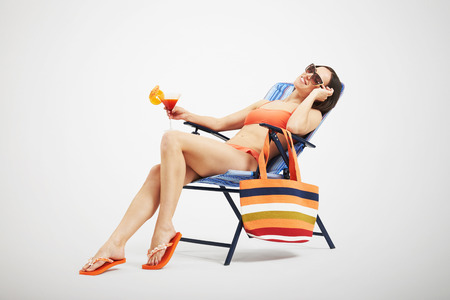 chaise longue: beautiful slim woman in bikini and sunglasses relaxing on beach chair and holding cocktail over light background Stock Photo