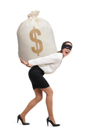 illegality: laughing woman in formal wear and black mask on the eyes holding big bag with money and looking at camera. isolated on white background