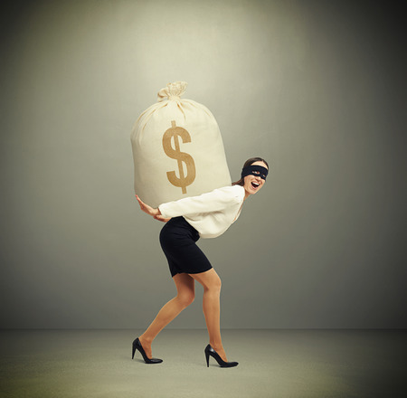 delinquency: laughing woman in formal wear and black mask on the eyes holding big bag with money and looking at camera against grey background