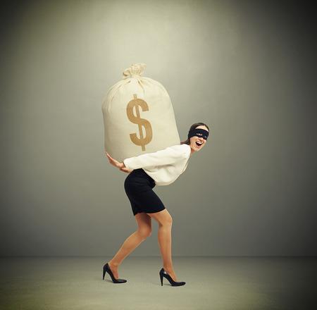 delincuencia: mujer riendo en ropa formal y la máscara de negro en los ojos que sostienen gran bolsa con dinero y mirando a la cámara contra el fondo gris