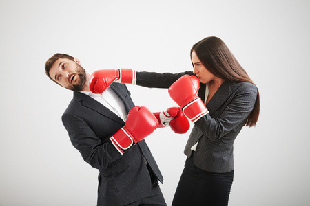duel: angry businesswoman in red boxing gloves punching businessman over light grey background Stock Photo