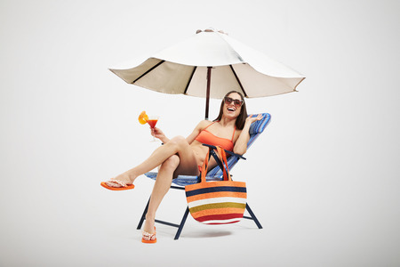 chaise longue: beautiful laughing woman in bikini and sunglasses relaxing on beach chair and holding cocktail under beach umbrella over light background
