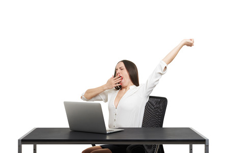 tiresome: tired woman sitting with laptop and yawning over white background