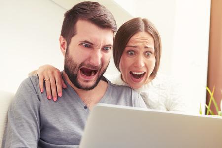 Fotografia interna di coppia urlata sorpreso guardando laptop Archivio Fotografico - 40300556