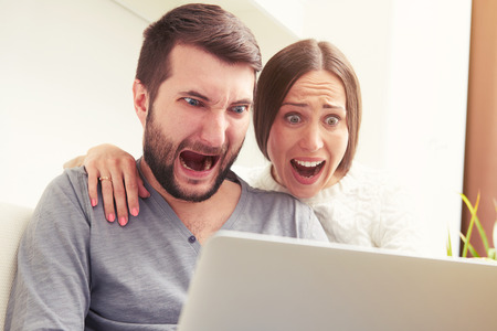 indoor photo of amazed screaming couple looking at laptop