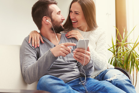young adult couple listening to music together, laughing and looking at each other