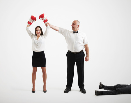 referee holding happy winner businesswoman in boxer gloves and looking at her, near lying knocked out businessman over light grey background