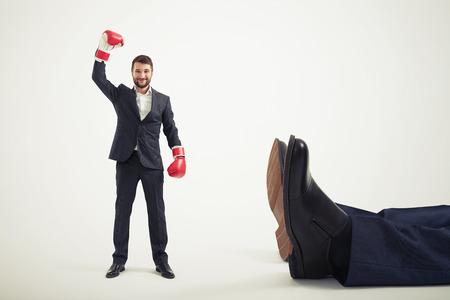 smiley winner businessman in red boxing gloves standing near big lying mans legs over light grey background Foto de archivo