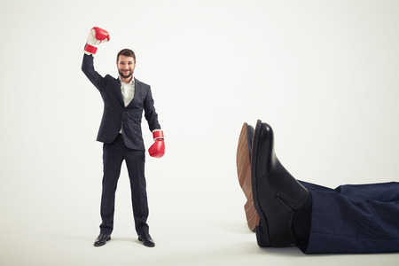 smiley winner businessman in red boxing gloves standing near big lying mans legs over light grey background Standard-Bild