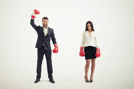 business rival: businesswoman loser and smiley winner businessman in red boxing gloves isolated on white background