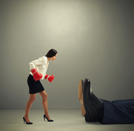 knocked over: angry businesswoman in formal wear and boxer gloves looking at big knocked out man over dark grey background