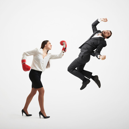 angry businesswoman in formal wear and red boxing gloves punching businessman over light grey background