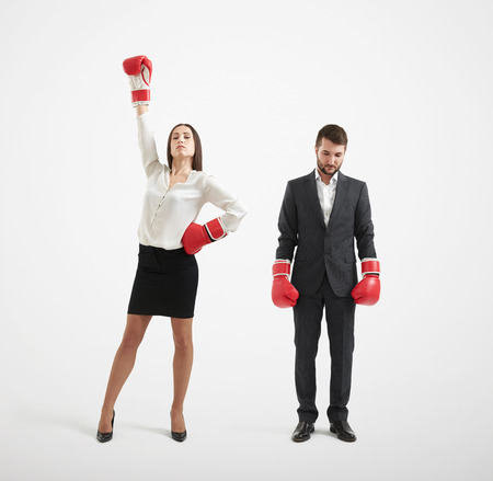 losers: businessman loser and winner businesswoman in red boxing gloves over light grey background Stock Photo