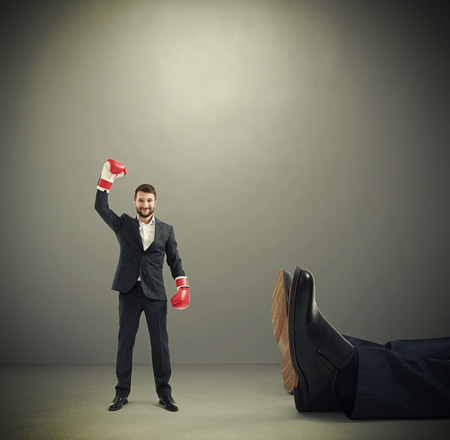 happy winner businessman in red boxing gloves standing near big lying mans legs over dark grey background Stok Fotoğraf