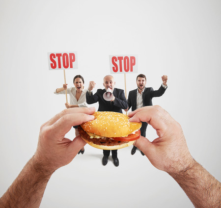 woman shouting: concept of harmful fast foods. small people screaming and holding placard with stop sign, big hands holding fat burger and ready to eat it Stock Photo