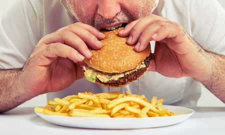 close up photo of man eating burger and french fries Standard-Bild