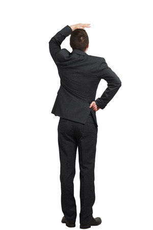 back up: back view of businessman in black suit looking up and covering one hand over white background