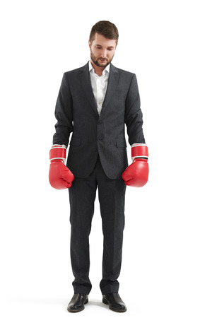 doleful: sad businessman in formal wear and red boxing gloves over white background