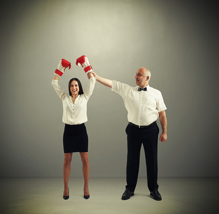 duel: referee holding winner businesswoman in boxer gloves and looking at her over dark grey background Stock Photo