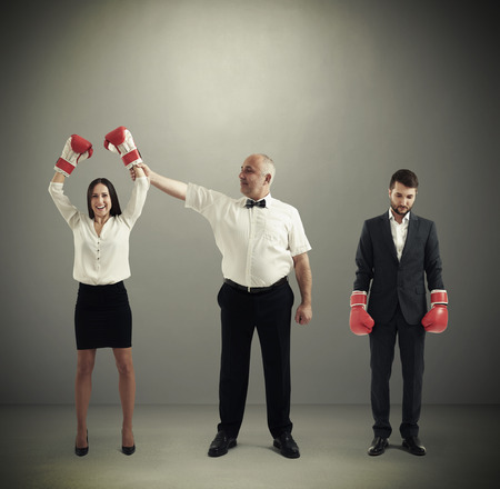 referee holding winner businesswoman in boxer gloves and looking at her, near standing sad loser businessman over dark grey background