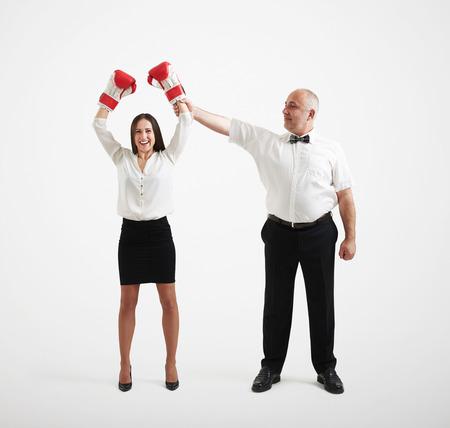 arbitros: smiley árbitro sostiene feliz ganador empresaria en los guantes del boxeador y mirándola, aislado sobre fondo gris claro Foto de archivo