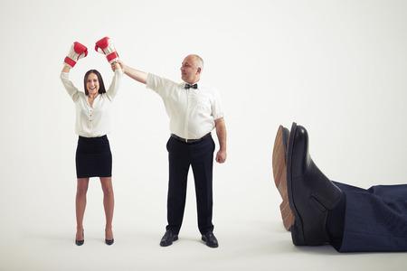 knocked out: �rbitro sonriente sosteniendo ganador empresaria en los guantes del boxeador y mir�ndola, cerca acostado grandes piernas de hombre de negocios fuera de combate. aislado en fondo gris claro