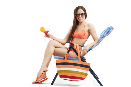 deck chair: beautiful smiley woman in bikini and sunglasses relaxing on beach chair and holding cocktail over light background