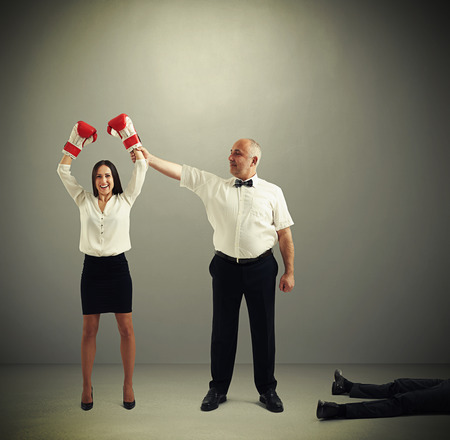 knocked over: referee holding winner businesswoman in boxer gloves and looking at her, near lying knocked out businessman over dark grey background