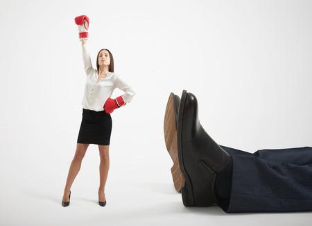 winner businesswoman in red boxing gloves standing near big lying mans legs over light grey background