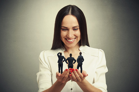 henpecked: smiley woman holding three men on her palms and looking at them over dark background