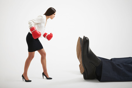 knocked over: angry businesswoman in boxer gloves looking at big knocked out businessman over light grey background