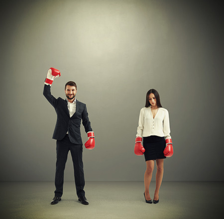 loser: sad businesswoman loser and happy winner businesswoman in red boxing gloves over dark grey background