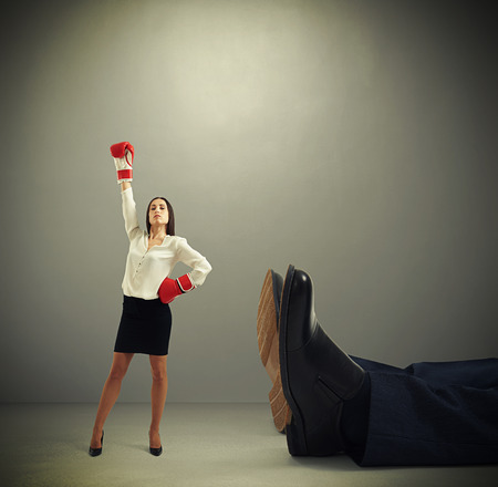 winner businesswoman in red boxing gloves standing near big lying mans legs over dark grey background Stock Photo