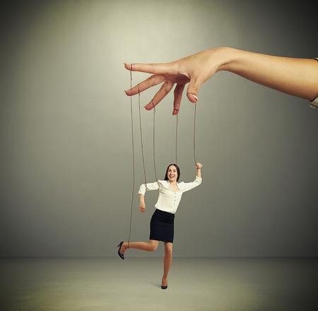 marioneta: mujer títere manipulación mano sobre fondo oscuro