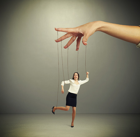 puppet woman: womans hand manipulating puppet over dark background Stock Photo