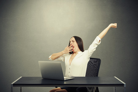 tiresome: tired woman sitting with laptop and yawning over dark background Stock Photo